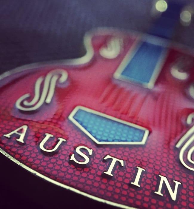 Burgundy Blues electric guitar with Austin lettering on body near Marq on Burnet in Austin, Texas