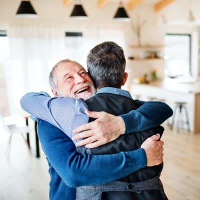 Father and son embrace at Arbor Glen Senior Living in Lake Elmo, Minnesota