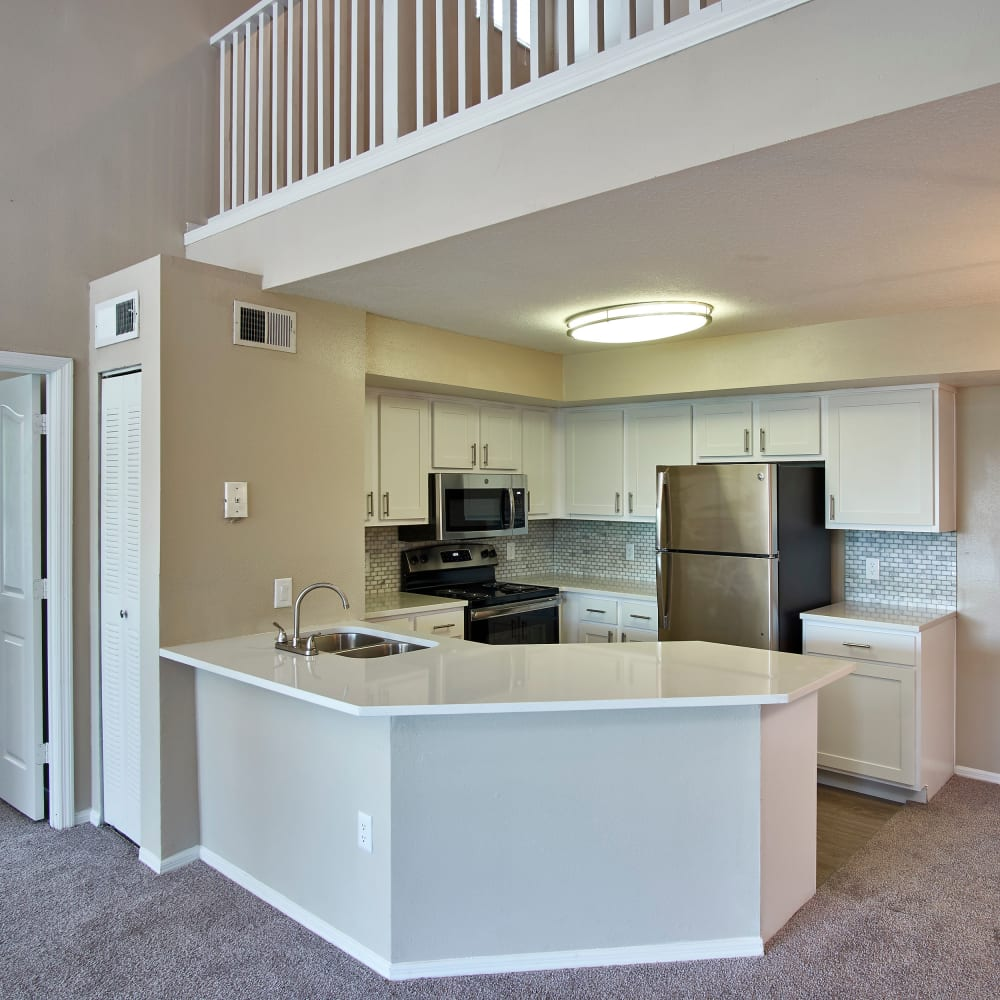 A kitchen with a breakfast bar at Calais Park Apartments in St Petersburg, Florida
