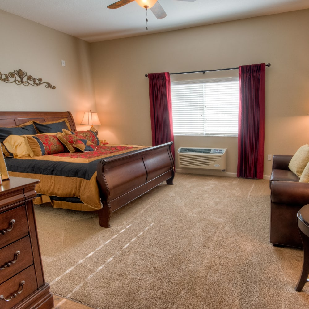 Resident bedroom with carpeting at Inspired Living in Kenner, Louisiana