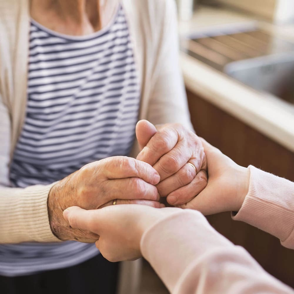 Resident holding hands with a caretaker at Anthology Senior Living in Chicago, Illinois