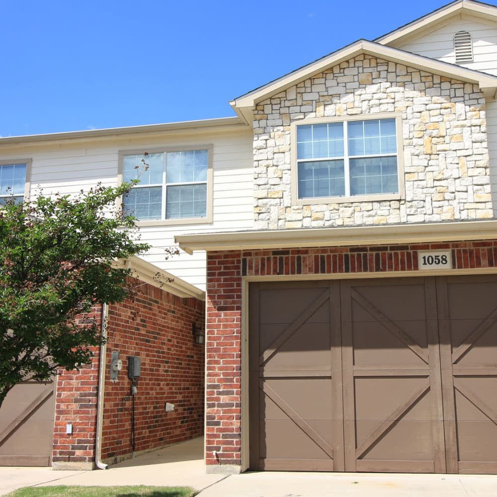 Private garage next to a townhome's entrance at Oaks Estates of Coppell in Coppell, Texas
