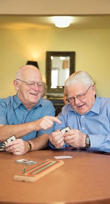 Elders play a game of cards at The Enclave at Cedar Park Senior Living in Cedar Park, Texas