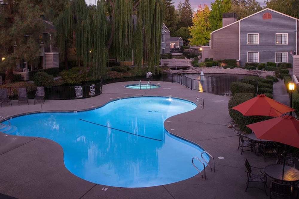 Spacious sundeck with table and chairs next to a swimming pool at Hidden Lake Condominium Rentals in Sacramento, California