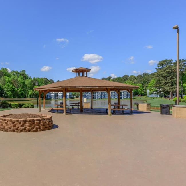 Expansive covered gazebo and fire pit area near the lake at The Bentley at Marietta in Marietta, Georgia