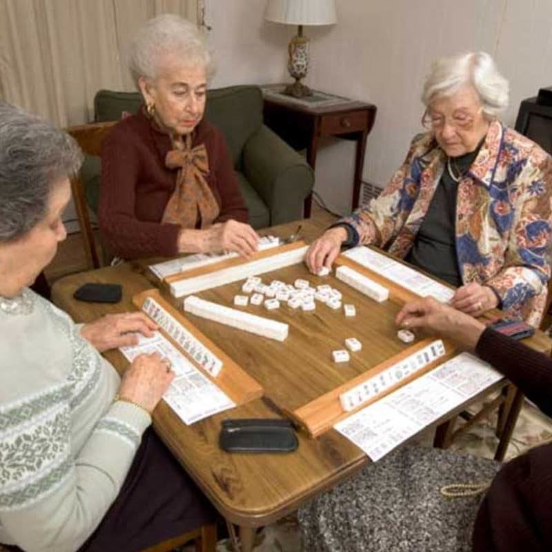 A group of seniors playing dominoes at Peninsula Reflections in Colma, California
