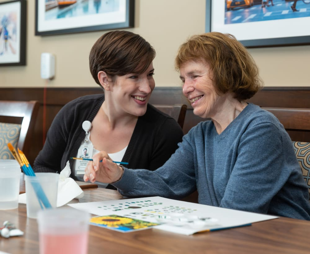 A resident and caretaker painting at Touchmark at Meadow Lake Village in Meridian, Idaho