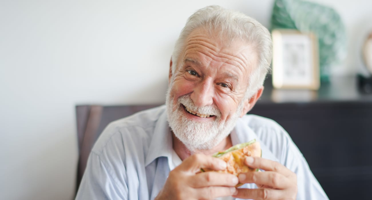 Resident enjoying a burger at Windsor in Dallas, Texas.