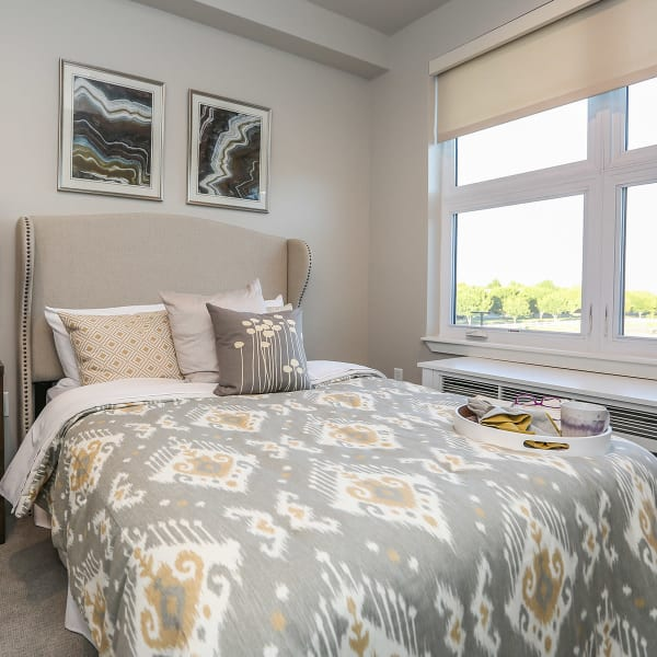 Furnished bedroom with a large bed inside an apartment at Quail Park at Morrison Ranch in Gilbert, Arizona