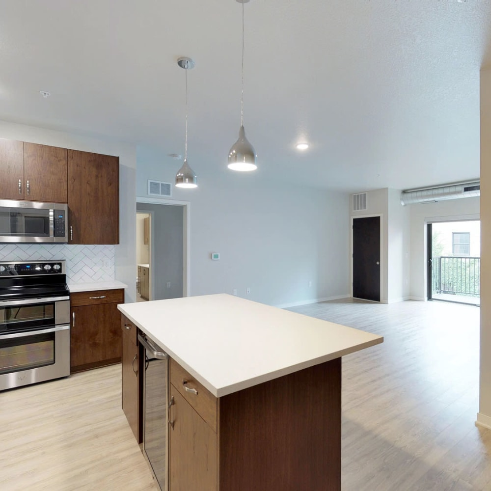 Spacious open-concept floor plan with hardwood floors and quartz countertops in the kitchen at Oaks Union Depot in St. Paul, Minnesota