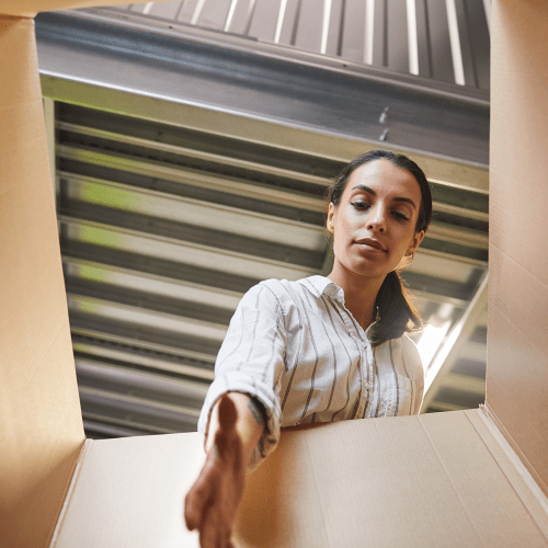 Woman reaching into box inside a climate-controlled unit at A-American Self Storage in Lancaster, California