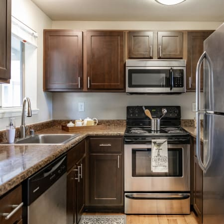 Latitude Apartments brown renovated kitchen with stainless steel appliances