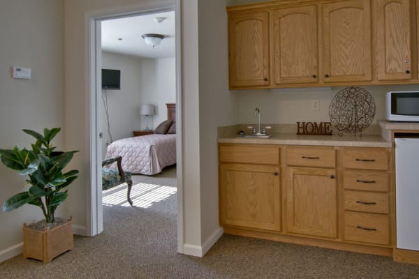Assisted living apartment kitchen with a view of the bedroom at Churchill Terrace in Fulton, Missouri
