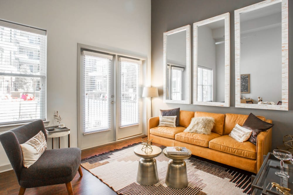 Full size couch, coffee tables, sitting chairs with large, tall mirrors on wall at Marq Midtown 205 in Charlotte, North Carolina