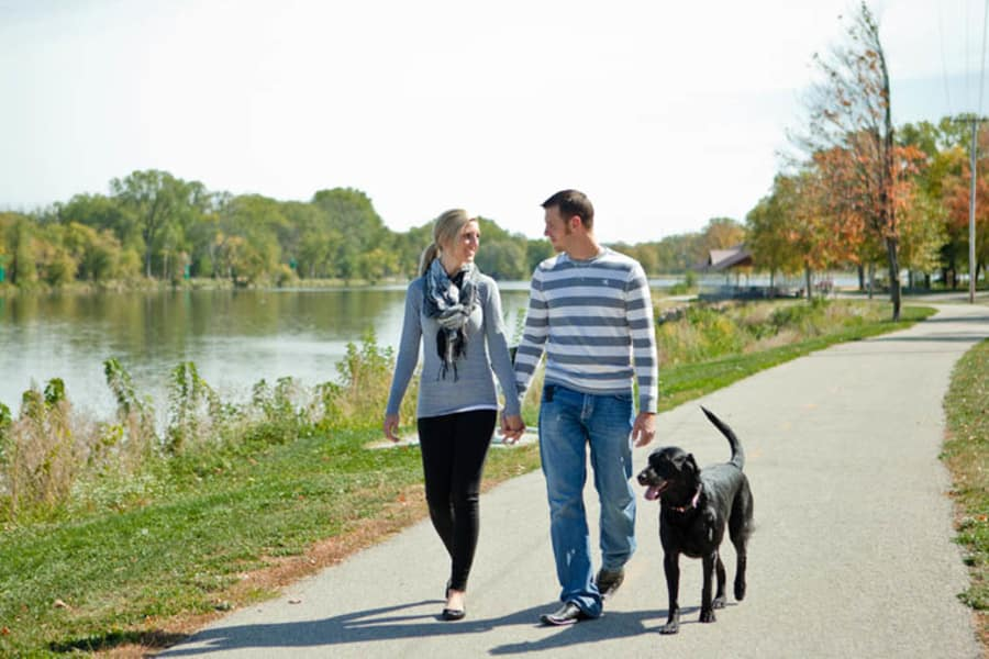 Couple walking dog near Windsor on the River in Cedar Rapids, Iowa