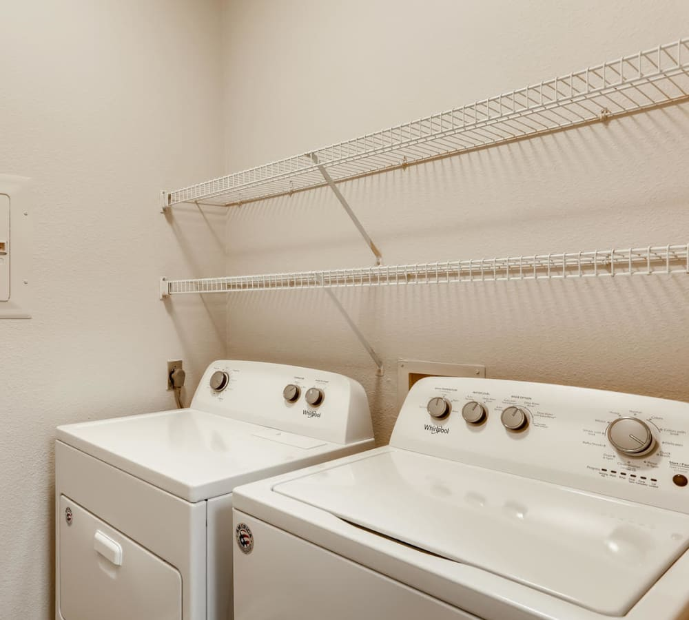 Laundry room with storage racks at Alize at Aliso Viejo Apartment Homes in Aliso Viejo, California