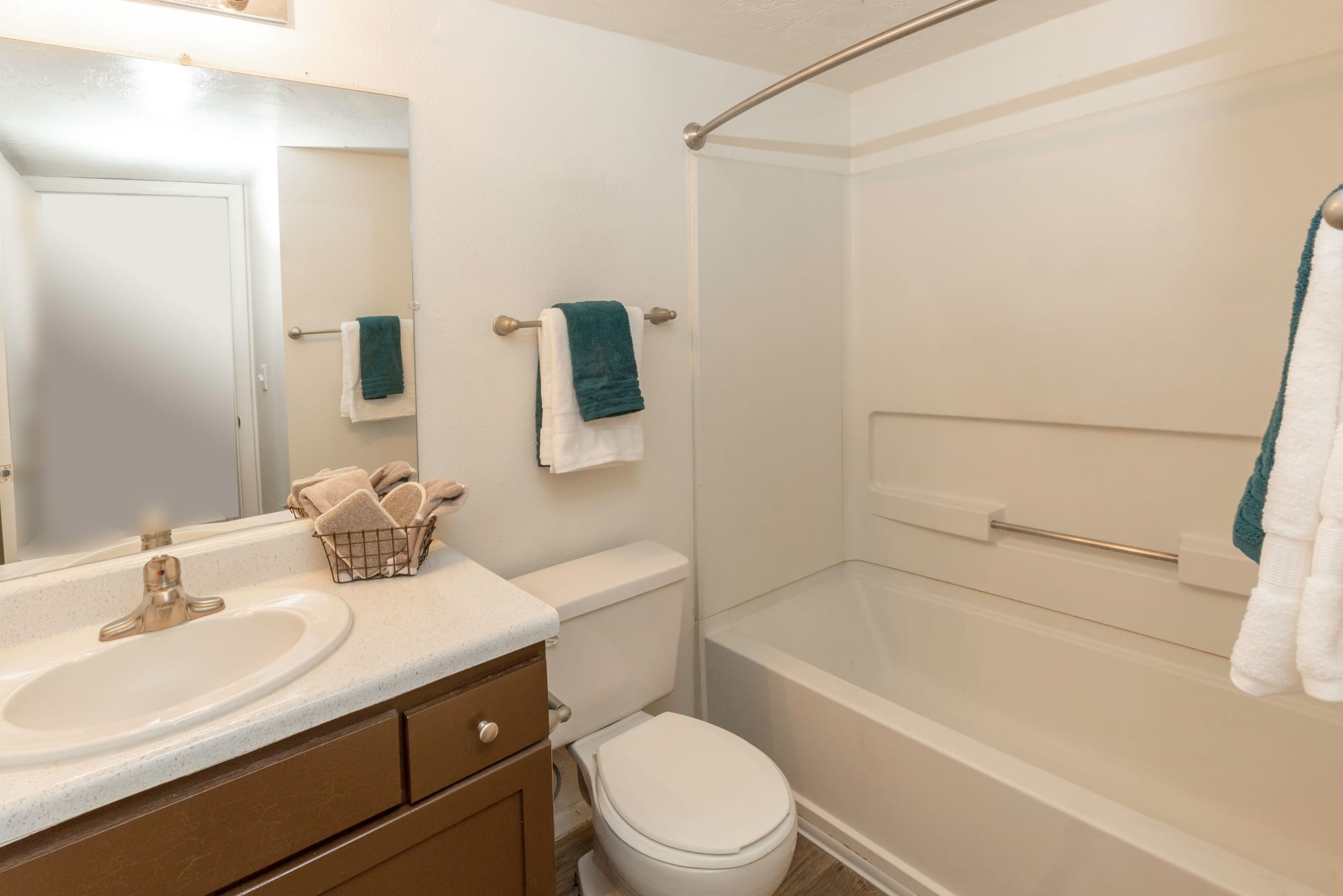 Renovated bathroom with brown cabinets and a tub at Windgate Apartments in Bountiful, Utah