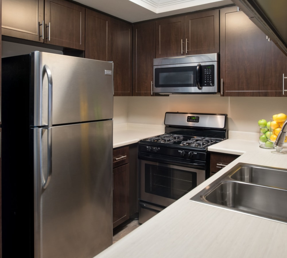 Kitchen with wood-style cabinetry at Shadow Ridge Apartment Homes in Simi Valley, California