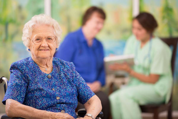 A woman resident sitting down at Heritage Senior Living and their signature programming.