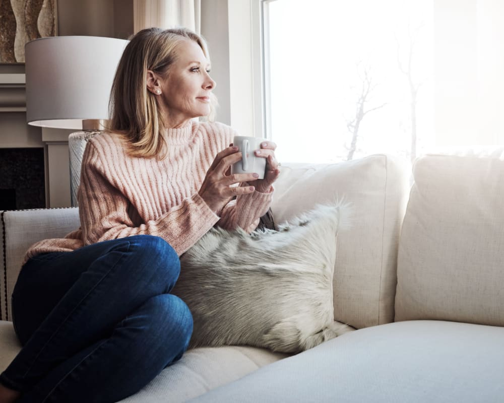 Resident enjoying coffee while sitting on her couch at Eagle Rock Apartments at Woodbury in Woodbury, New York