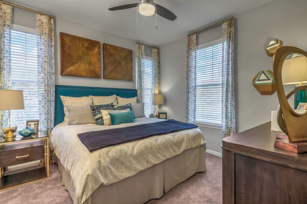 Master bedroom with a ceiling fan and an en suite bathroom in a model home at The Palmer in Charlotte, North Carolina