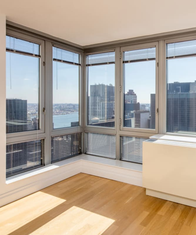 A living room with wood-style flooring and floor-to-ceiling windows at The Metropolis in New York, New York