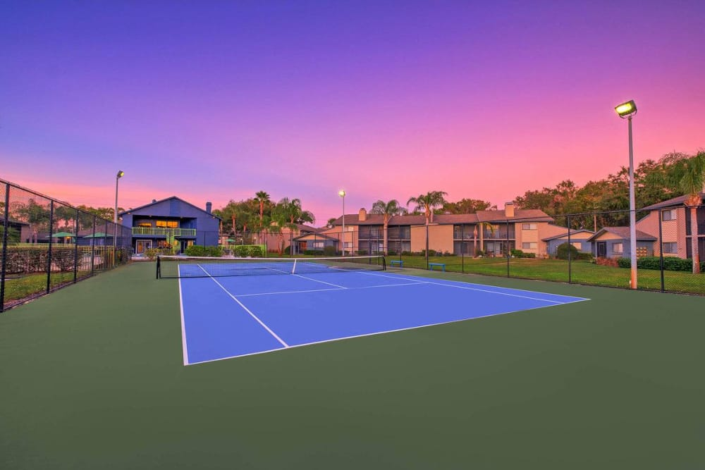 Twilight view of tennis court at WestEnd At 76Ten in Tampa, Florida
