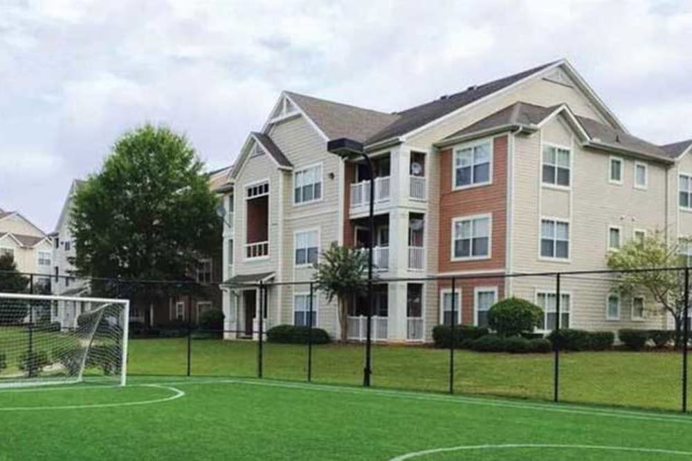 Exterior view of the buildings and soccer field at Belle Vista Apartment Homes in Lithonia, Georgia
