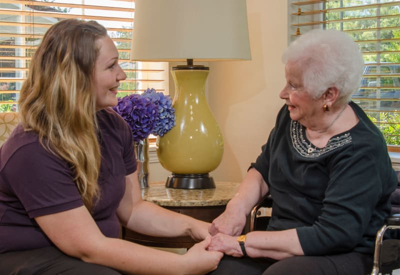 A caregiver and a resident holding hands at Carefield Living.