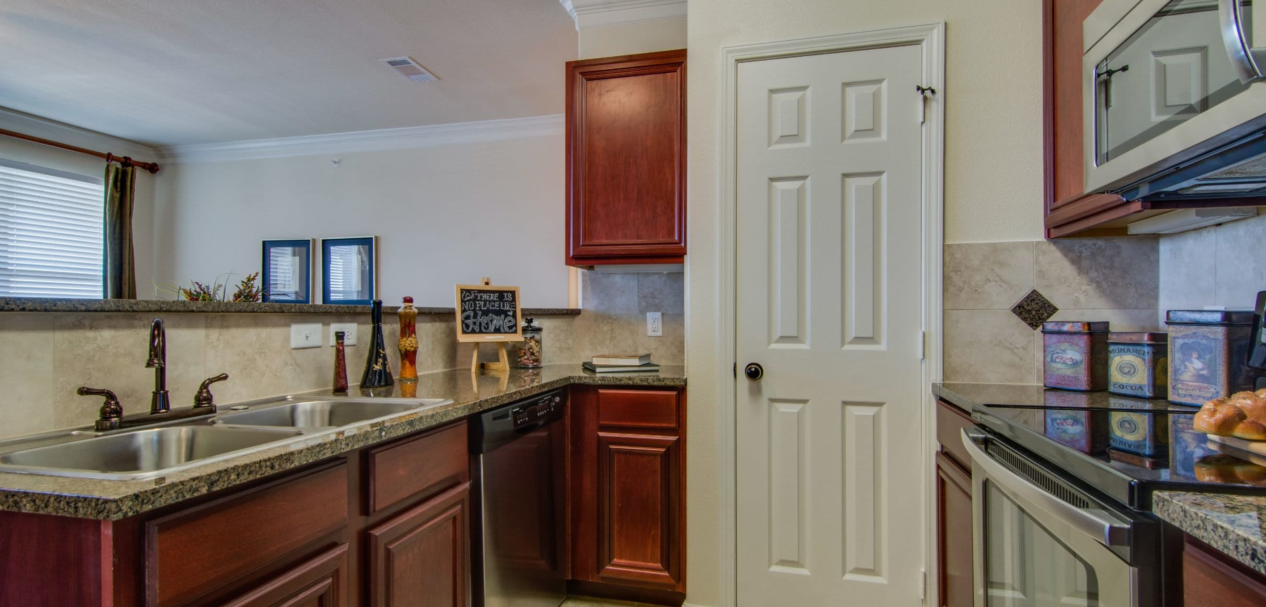 Kitchen with granite style counters at Marquis Rockwall in Rockwall, Texas