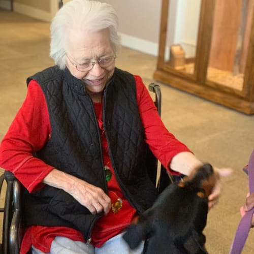 A resident petting a dog at FountainBrook in Midwest City, Oklahoma