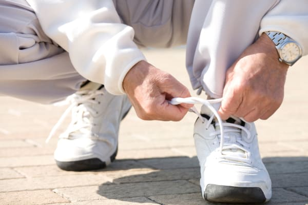 Senior man tying his shoelace at Arbors Memory Care in Sparks, Nevada