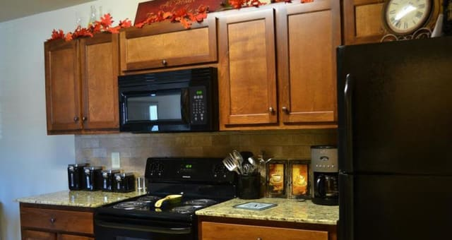 Sleek black appliances at The Grove at Stone Park in Pike Road, Alabama stand out among the cabinetry.