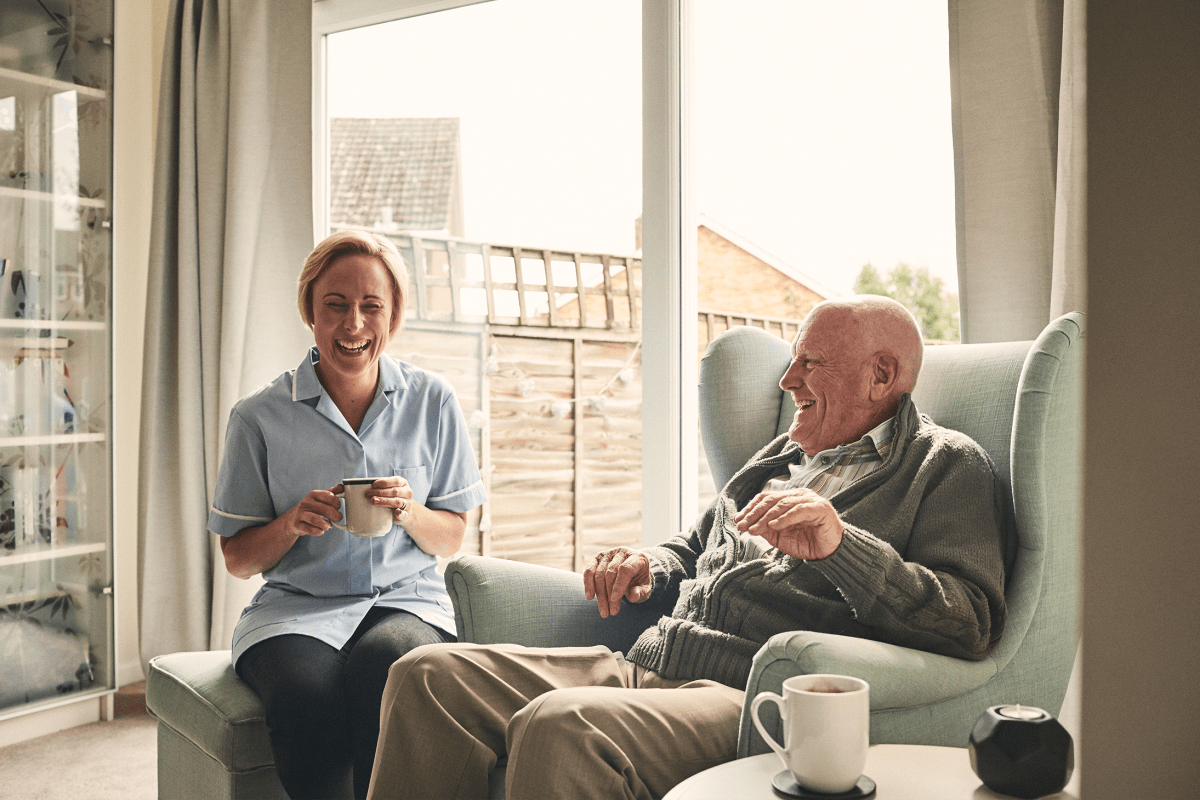 A caregiver having coffee with a resident at Milestone Retirement Communities