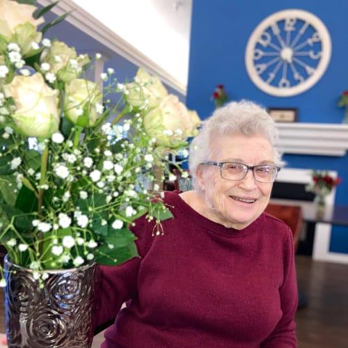 Resident smiling with flowers at Madison House in Norfolk, Nebraska