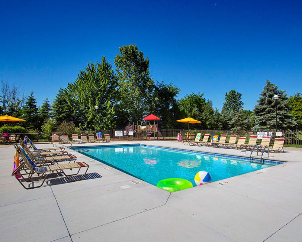 Pool with lounge chairs surrounded by luscious trees at Stone Crest in Mt Pleasant, Michigan
