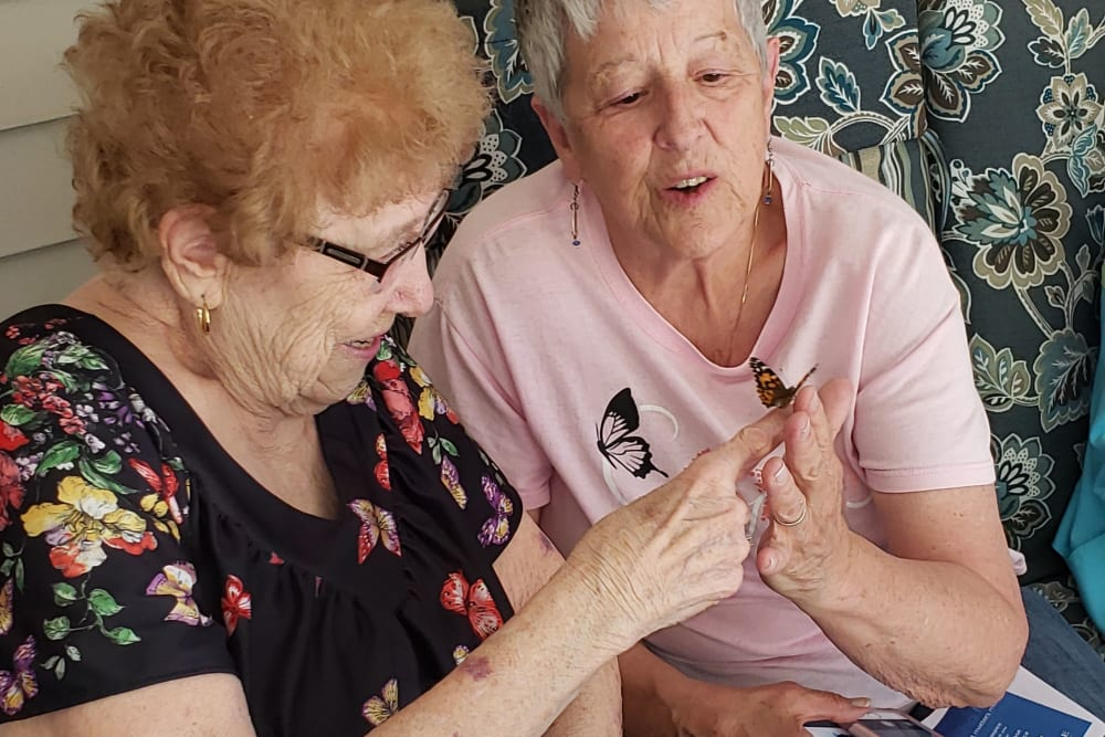 Residents admire a butterfly in someone's hand at Landings of Blaine in Blaine, Minnesota