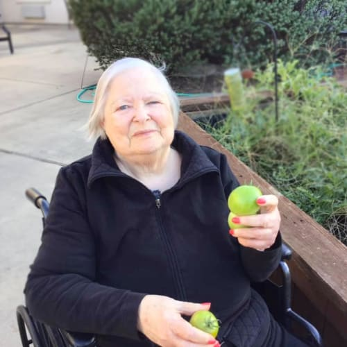 Resident holding fresh apples outside at Oxford Glen Memory Care at Grand Prairie in Grand Prairie, Texas