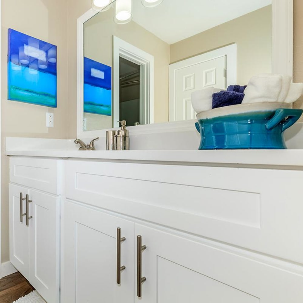 Large vanity mirror and ample cupboard space in the newly renovated bathroom of a model home at The Bentley at Marietta in Marietta, Georgia