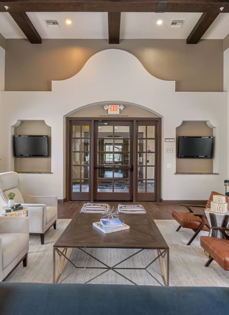 Community clubhouse lounge area with large screen television monitors at Marquis at Sonoran Preserve in Phoenix, Arizona