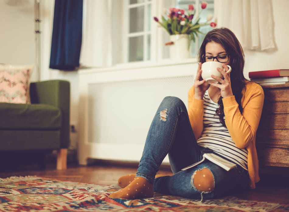 Resident sipping a warm cup of tea in her apartment home at Sofi at 50 Forest in Stamford, Connecticut