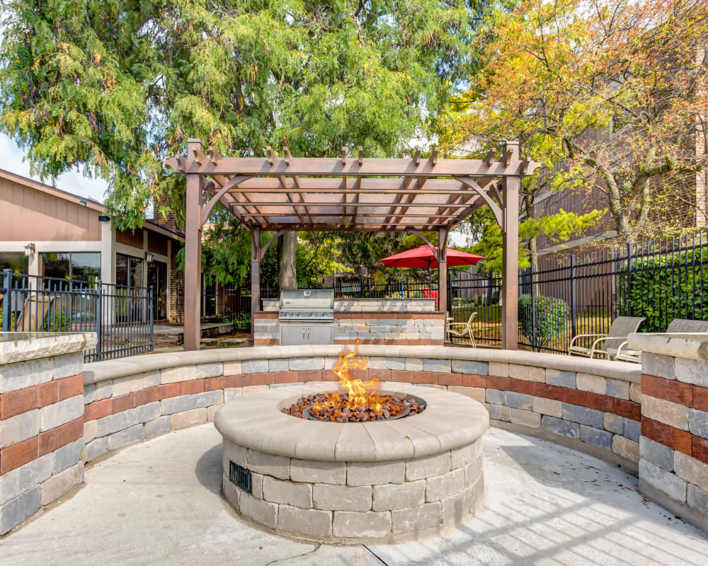Outdoor fire pit with grill in the background at Lakeside Apartments in Wheaton, Illinois