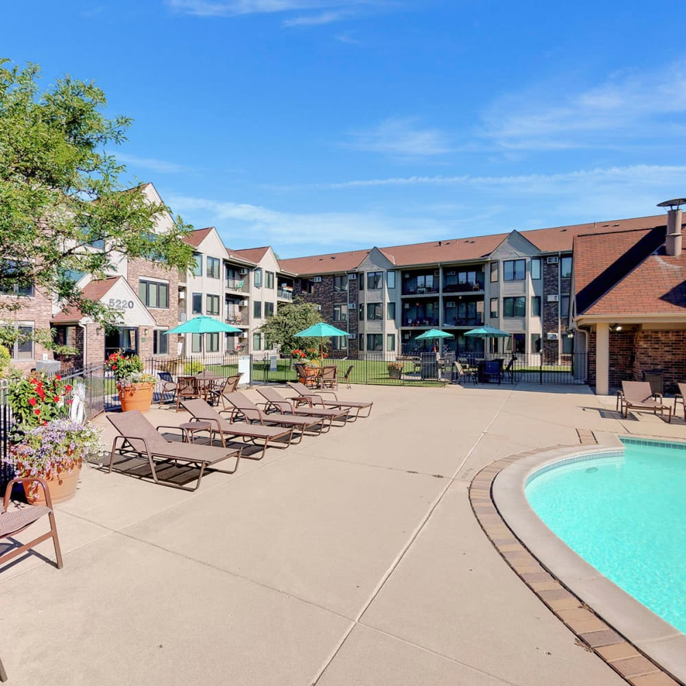 Lounge chairs near the pool on a beautiful day at Oaks Lincoln Apartments & Townhomes in Edina, Minnesota