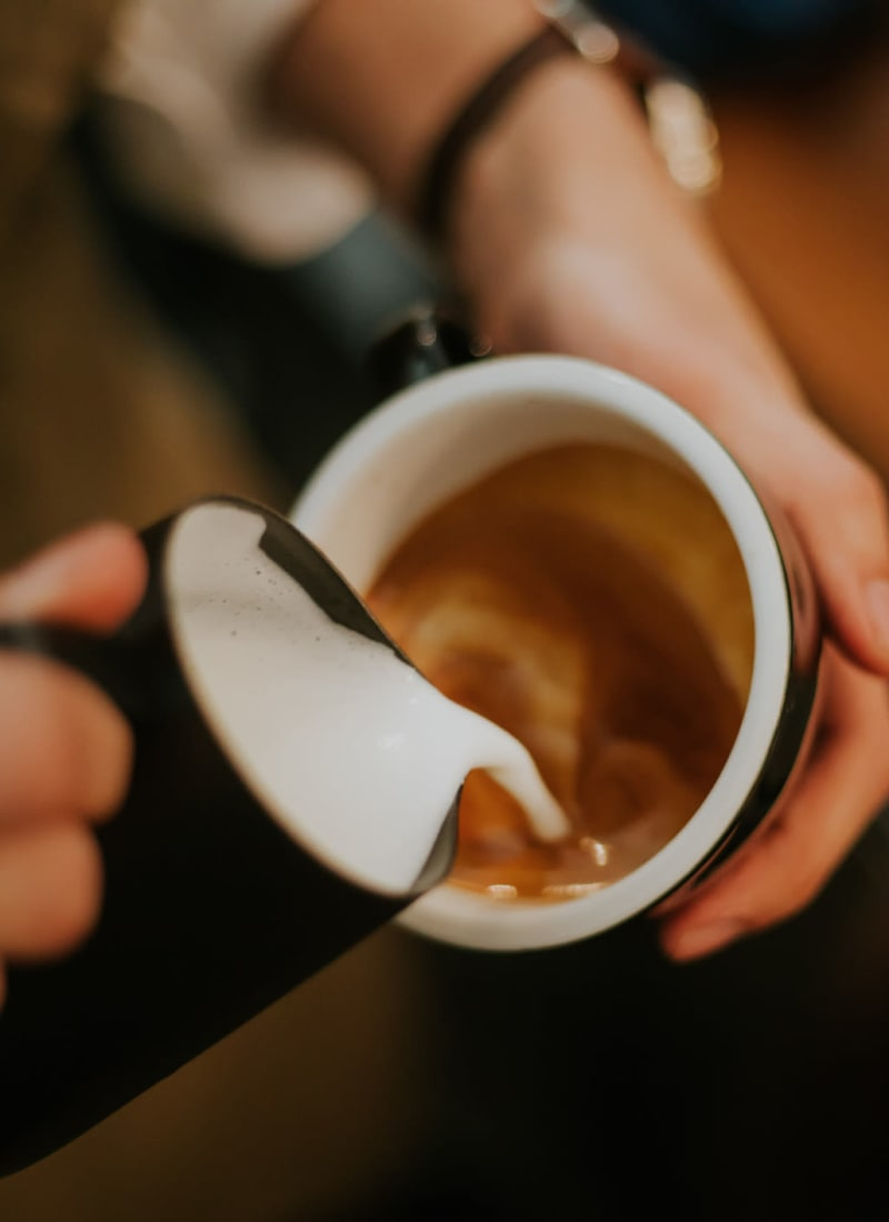 Barista preparing a latte near Marquis at Kingwood in Kingwood, Texas