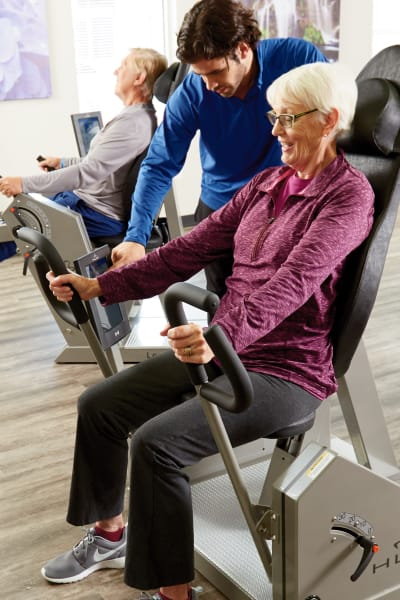 Gym instructor assisting a resident on a workout machine at Quail Park of Lynnwood in Lynnwood, Washington
