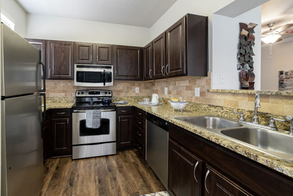 Modern style kitchen with granite counters at Marquis at Bellaire Ranch in Fort Worth, Texas