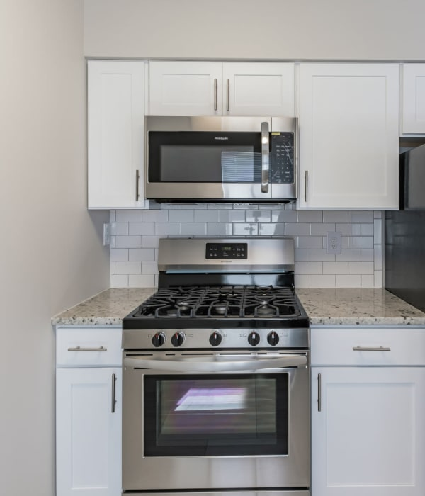White wooded cabinets in the kitchen with tons of space on counters for cooking and baking at Eagle Rock Apartments at North Plainfield in North Plainfield, New Jersey