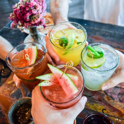 Friends toasting fruity drinks near Marq on Ponce in Atlanta, Georgia