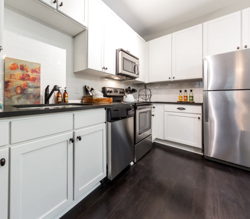 Modern style kitchen with white cabinets and stainless steel appliances at Marquis at Buckhead in Atlanta, Georgia