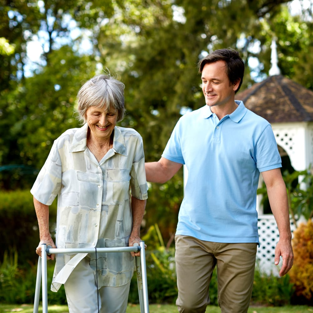 A caregiver and a resident out for a walk at Inspired Living Delray Beach in Delray Beach, Florida